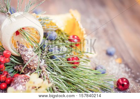 Festive scene with fir branches, blueberries, Christmas balls in a powdered waffle cone on rustic wooden background, Copy space, vintage decoration