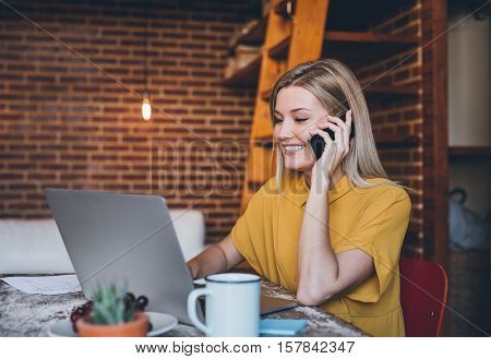Attractive young blonde woman sitting at table in her modern loft apartment talking on a cellphone and using a laptop