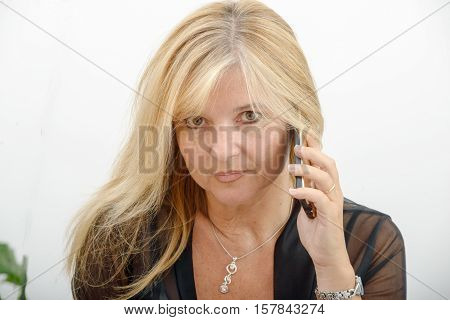 beautiful mature blond woman talking on mobile phone