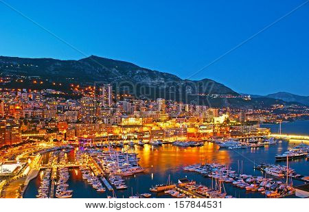 Panorama of the Hercules Port with the yachts and boats surrounded by thousands of city lights reflected in water Monaco.