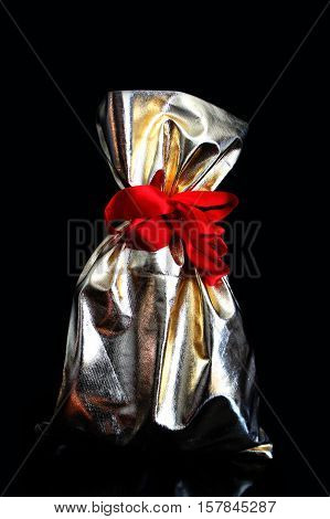 Golden gift bags tied with a red ribbon on a black background.