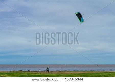 Young man kites a kite during sunset on the coast of the Rio de la Plata, Argentina
