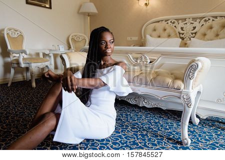 attractive african woman in the luxury european hotel. Model sitting on the floor covered with blue carpet. She put her hands on knee. Hotel room is designed in classic style.