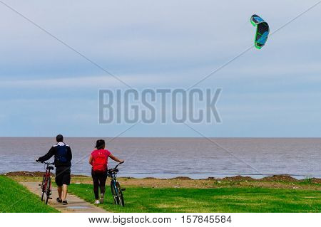 Two Young People Walk With Their Bikes With A Kiteboard In The Background On The Coast Of The Rio De