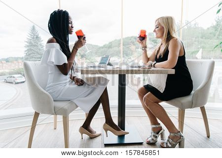 two attrsvtive women drinking wine and chatting in a restaurant in front of the big windows. European and african women have a good day. African girl is in white, blonde girl is in black dress. White and green decoration. Luxury interior