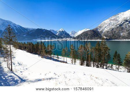 Idyllic snow landscape with mountain lake Achenlake Achensee Austria Tirol.