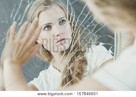 Teenage girl with personality disorder touching broken mirror