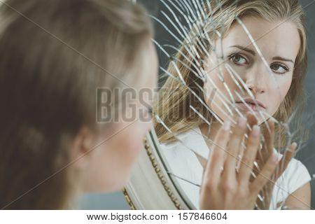 Beautiful woman with mental disorder touching broken mirror