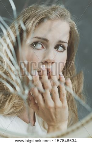 Broken mirror reflection of beutiful sad woman
