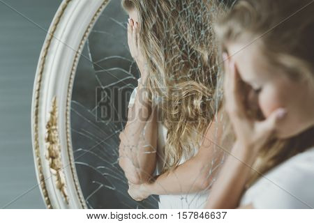 Girl with mental disorder covering her face reflected in mirror