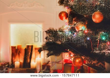 Beautiful holdiay decorated Christmas tree near fireplace, closeup in modern living room. Shining lights, balls and garland on fir tree. Winter holiday night magic. Design and decorations background