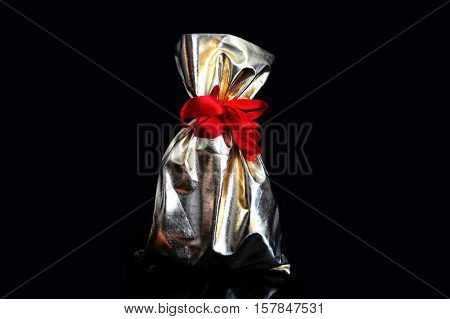 Golden gift bags tied with a red ribbon on a black background