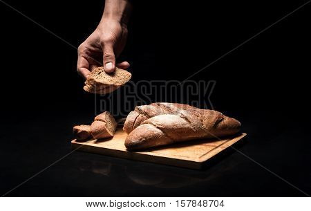 Soft and crunchy. Close up of mans hands holding the baguette while cooking and preparing a dish in a restaurant.