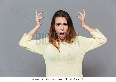 Portrait of an angry irritated woman with hands raised shouting at camera isolated on the gray background