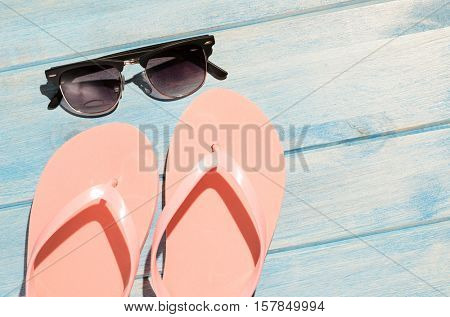 pink flip flops and sunglasses on blue wooden table with sunlight