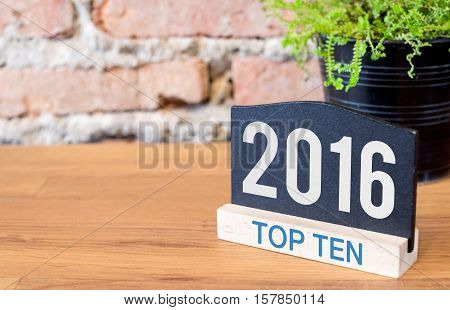 Top ten topic of 2016 year on blackboard sign and green plant on wood table at brick wall