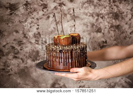 Woman holding chocolate cake with apples on grey background
