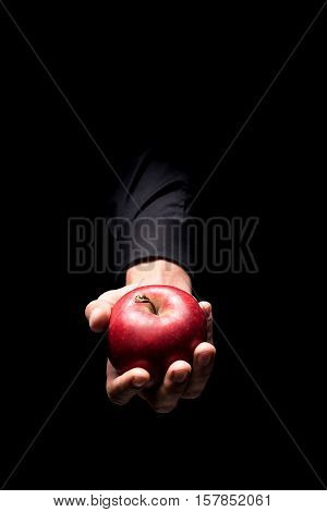 Delicious fruit. Close up of mans hand holding a red big apple and standing on black background while demonstrating it.