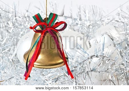 Golden Christmas bell on the white unfocused background
