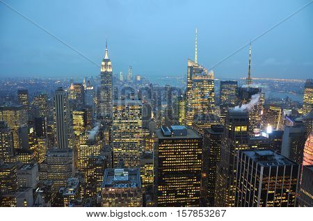 Manhattan Skyline and Empire State Building, viewed from Rockefeller Plaza at night, New York City, USA.