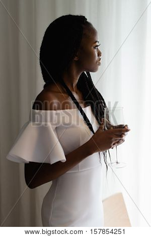 Close up photo of charming, touching, tender, beautiful african woman in restaurant staying in front of the big window. Girl is in whihe dress, has long dark hair and a glass of alcohol in her hands.