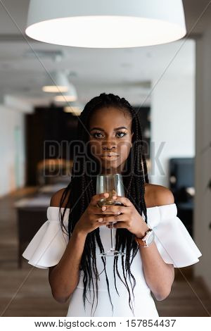 Close up photo of charming, touching, tender, beautiful african woman in restaurant. Girl is in whihe dress, has long dark hair and a glass of alcohol in her hands hear her face. Model is standing under the white chandelier and looking at the camera.