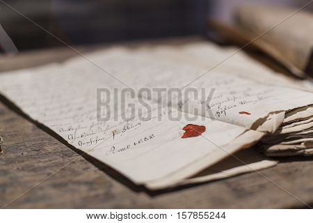 Stack of pages of old script handwritten aged paper with stains and folding signs red sealing wax extremely shallow depth of field