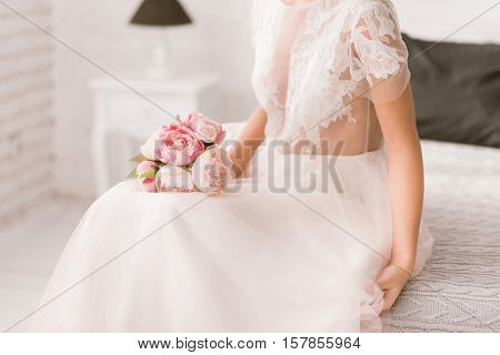 Wedding bouquet of peonies. Pleasant young bride sitting on the bed in white colored room while holding the bouquet of peonies and expressing tenderness