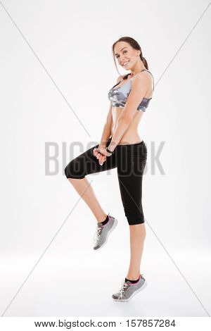 Full length fitness woman stands sideways. posong. looking at camera. so pretty girl. isolated white background