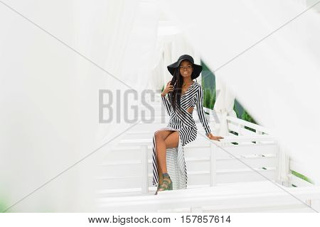 Sexy black woman sitting on the white fence. White light sunblind around.