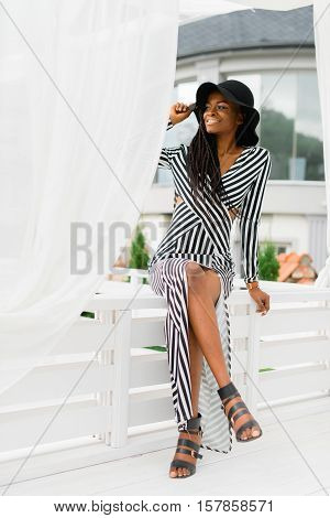 Sexy black woman sitting on the white fence. White light sunblind around. Beautiful teritory of luxury hotel. Model with beautiful legs.
