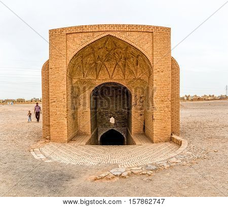 YAZD, IRAN - MAY 4, 2015: Disused building at the foot of the hill and the tourists passing by.