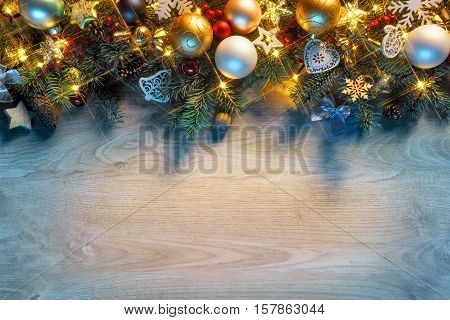 Christmas fir tree with lights on wooden background in dark. Merry Christmas and Happy New Year!! Top view.