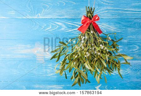 Bouquet from mistletoe on wood background. Christmas background