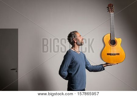 Portrait of man grizzled with classical guitar, wall background
