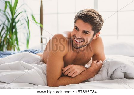 Wonderful morning. Happy young man is lying on bed and smiling