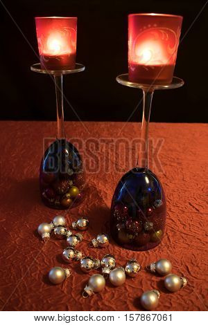 2 blue wine glasses on a red tablecloth decorated with silver Christmas balls. The wine-glasses stand on their heads and are filled with colorful Christmas balls. Each wine glass carries a red tea light holder.