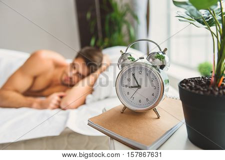 Relaxed young man is sleeping in bed in morning. Focus on clock