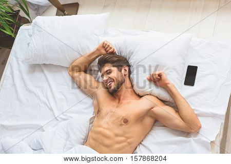 I am happy to wake up in the morning. Joyful young man is lying in bed near smartphone and stretching his arms. He is laughing