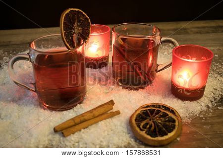 2 glasses with mulled wine in the snow with orange slices cinnamon sticks and 2 red tea light holders with ever a burning tea lights