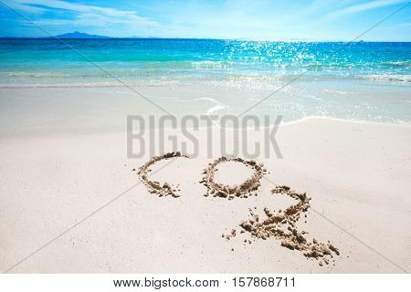 CO2 handwritten in sand on a tropical beach