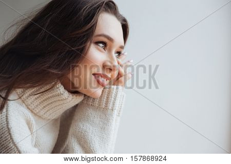 Side view of young model in sweater near the window. in profile.