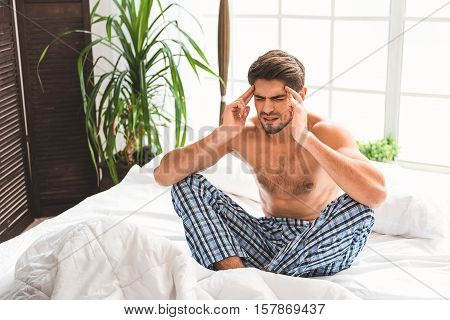 Stressed young man suffers from headache in bedroom. He is sitting and touching head with despair
