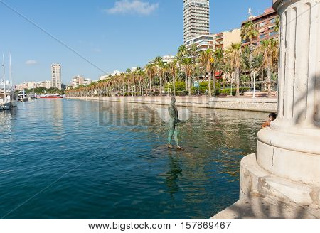 Alicante, Spain - September 9, 2016;  Icarus with broad shoulders with little head carrying a surf board in marina harbor. Alicante Spain