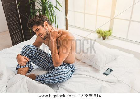 Young man suffers from pain in his neck. He is sitting on bed with desperation