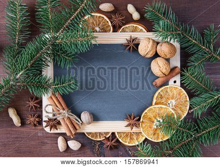 Christmas background: blank chalkboard surrounded by green fir branches and various spices nuts and dried oranges