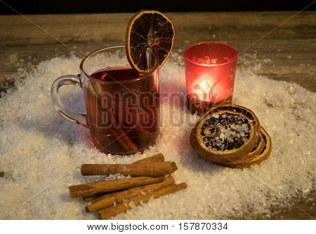 1 glass with mulled wine in the snow with orange slices cinnamon sticks and a red tea light holder with a burning tea light