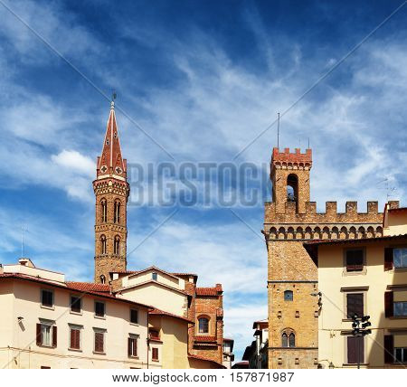 Bell tower of the Badia Fiorentina church and the Volognana Tower of the Palazzo del Bargello on blue sky background. View from the Piazza San Firenze at historic center of Florence Tuscany Italy. poster
