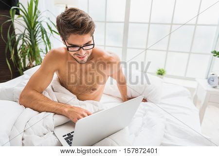 Do not get out of bed and keep communicating. Carefree young man is using laptop and laughing