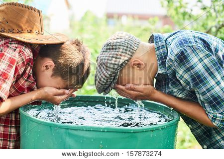 Two brothers wash your face in the water barrel on the farm
